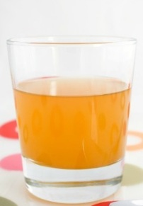 "A glass of raw unfiltered apple cider vinegar with ""mother""."